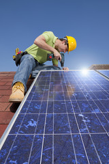 Engineer installing solar panel on rooftop with drill