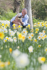 Portrait of smiling man hugging dog in sunny daffodil field
