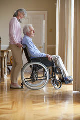Smiling senior woman standing behind senior man in wheelchair at window