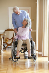Man holding hands with senior woman in wheelchair