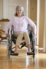Portrait of smiling senior woman in wheelchair