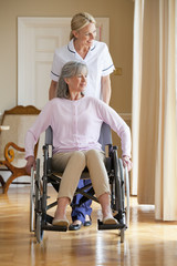 Smiling home caregiver pushing senior woman in wheelchair