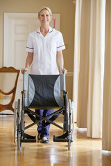 Portrait of smiling home caregiver with wheelchair in corridor