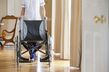 Home caregiver with wheelchair in corridor