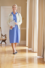 Portrait of smiling home caregiver holding medical record in corridor