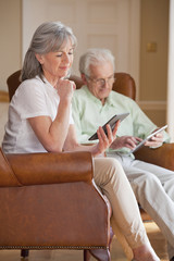 Senior couple using digital tablets in armchairs