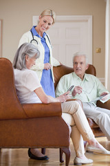 Smiling home caregiver talking to senior couple with digital tablets in armchairs