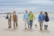 Group Of Mature Friends Walking Along Beach Together