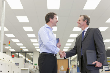 Smiling businessmen shaking hands in hi-tech electronics factory