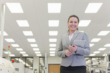 Portrait of smiling businesswoman holding digital tablet in hi-tech electronics factory