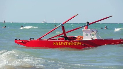 typical red rescue boat and swimmers, Rimini, Italy