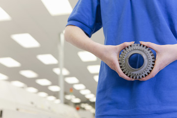 Close up of engineer holding gear wheel in hi-tech electronics factory
