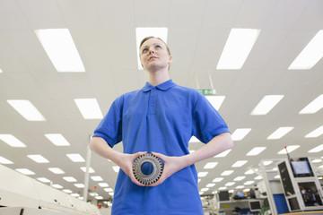 Engineer holding gear wheel in hi-tech electronics factory
