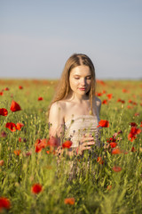 Woman at white dress taking red poppy