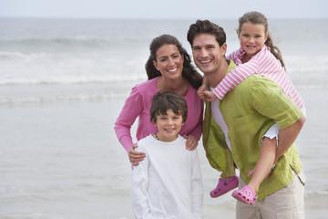 Family Walking Along Summer Beach