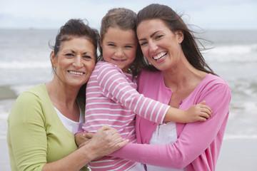 Mother, Daughter And Grandmother Walking Along Summer Beach