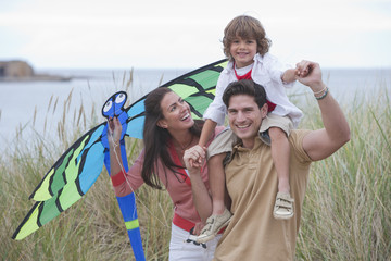 Family Flying Kite In Sand Dunes