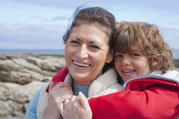 Grandmother And Grandson Exploring Rockpools Together
