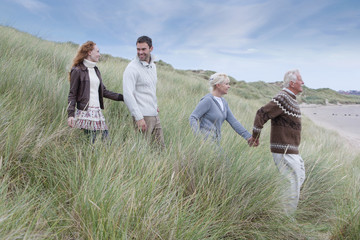 Parents With Adult Offspring Walking Through Dunes
