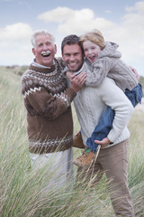 Grandfather, Father And Son Walking Through Dunes