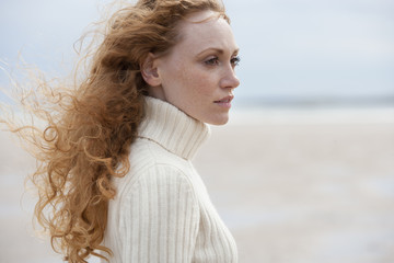 Thoughtful Woman Walking Along Winter Beach