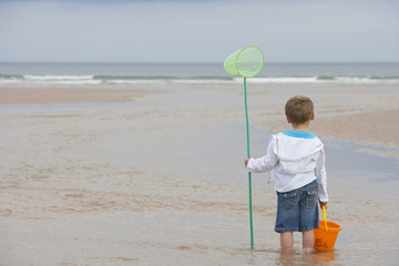Boy Playing In Sea With Fishing Net And Bucket