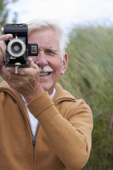 Portrait Of Senior Man With Old Fashioned Camera In Sand Dunes