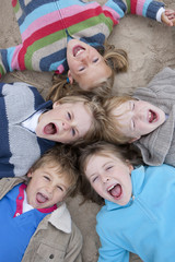 Overhead Shot Of Excited Children Lying On Beach