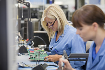 Technicians examining printed circuit boards in hi-tech electronics manufacturing plant