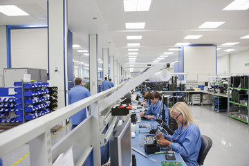 Technicians working on assembly line in hi-tech electronics manufacturing plant