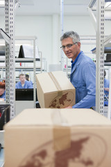 Worker lifting cardboard box in factory