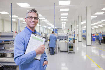 Portrait of smiling engineer with clipboard in hi-tech manufacturing plant