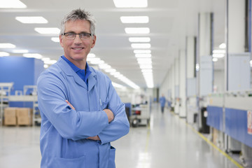 Portrait of smiling technician with arms crossed in hi-tech manufacturing plant