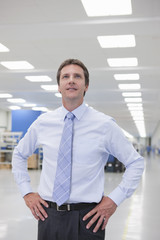 Portrait of confident businessman with hands on hips in hi-tech manufacturing plant