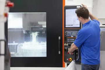 Technician operating lathe cutting machine in hi-tech manufacturing plant