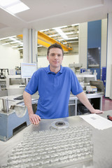 Portrait of smiling technician with aluminum products in hi-tech manufacturing plant