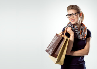 Happy smiling trendy female shopper with shopping bags
