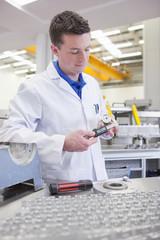 Scientist measuring aluminum product with vernier caliper in hi-tech manufacturing plant