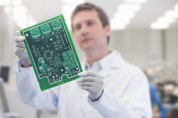 Close up of engineer holding printed circuit board in manufacturing plant