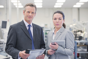 Portrait of confident businessman and businesswoman in manufacturing plant