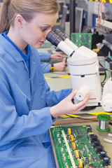 Technician using microscope to examine circuit board in manufacturing plant