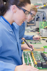 Close up of technicians soldering circuit boards in manufacturing plant