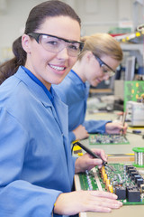 Portrait of smiling technician soldering circuit board in manufacturing plant