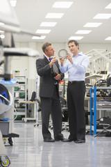 Businessmen examining machine part in manufacturing plant