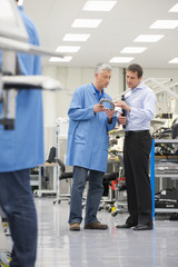 Businessman and engineer examining machine part in manufacturing plant