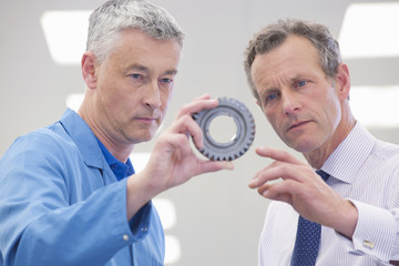 Close up of businessman and engineer examining machine part