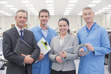 Portrait of confident business people and engineers in machine part manufacturing plant,