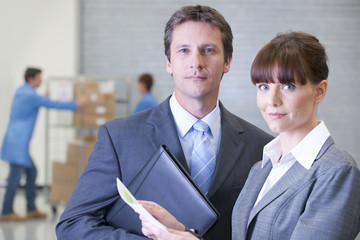 Portrait of confident businessman and businesswoman in warehouse