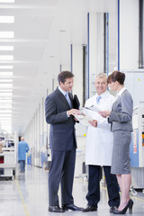 Business people and engineer reviewing paperwork in manufacturing plant