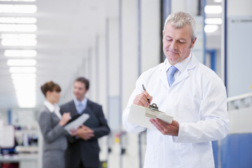 Engineer with clipboard in manufacturing plant